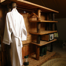 A shelf unit  with a safe and hanging space divides the bedroom from the bathroom area.