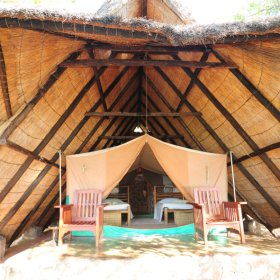 Each of the smaller tents are located under a vast thatched roof...