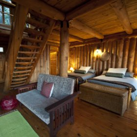 Each of the eight double-storey log cabins has an open plan lounge and a double bed.