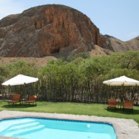 A large rock kopje creates an impressive back drop to the main area of Khowarib Lodge.