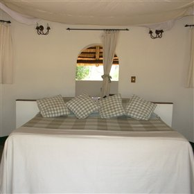 Twin or double beds are covered by a vast mosquito net at night.