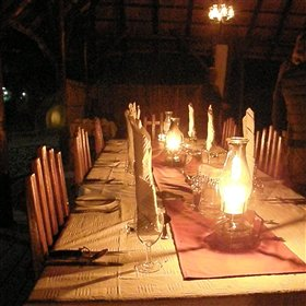 For dinner, guests and guides sit together on wooden decking by the river