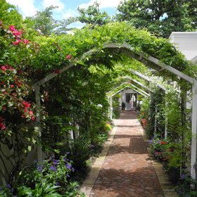 A narrow paved walkway lined by boungainvilleas and roses lead to its entrance.