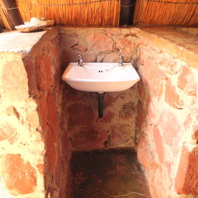 ... and a bathroom with a basin and toilet separated by a low wall ..