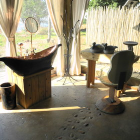 A mokoro shaped brass basin with a small vanity mirror looks out towards the river...
