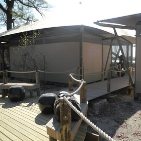 Raised wooden decks lead from the tents to the main areas.