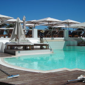 The main pool has lots of sun loungers and umbrellas and is surrounded by a wooden deck.