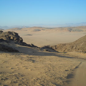 Travel through the sand dunes and mountains of Hartman's Valley on the way to Kunene Camp...