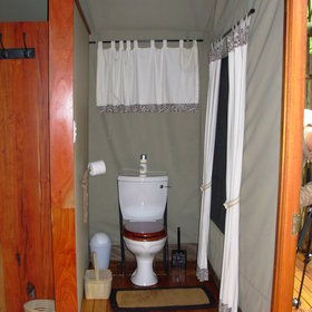 The toilet is divided from the room by a wall offering a little privacy.