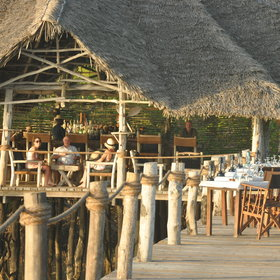 The main dining and lounge area are set on a raised platform above the beach ...