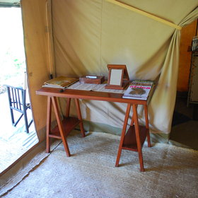 Other furniture consists of a writing table and directors' chairs on the veranda.