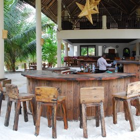 Near the bottom of the pool, the main beach bar is built on the sand.