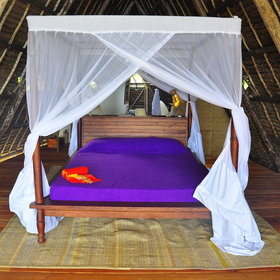Downstairs, there is the comfortable king size bed, drapped in mosquito nets…