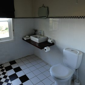 The bathroom features a shower, toilet and hand basin.