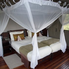 …and has a double bed enclosed by mosquito netting,…