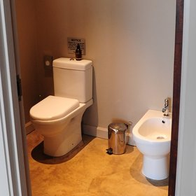 The toilet can be found in a separate little room.
