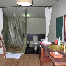 At the back of each tent is a spacious bathroom with toilet and bucket showers.