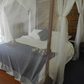 Inside is a double bed surrounded by a mosquito net.