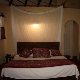 The bedroom has a double or twin bed surrounded by a mosquito net.