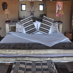 The tented rooms have wooden-frame double or twin beds...