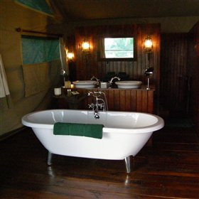 The bathrooms are open-plan, with twin sinks and bath, plus separate toilet and shower cubicles..