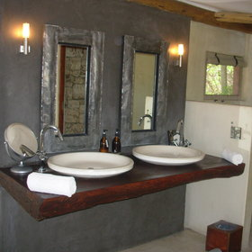 The en-suite bathroom comes with two sinks, a stone walk in shower ...