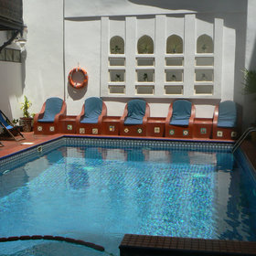 Surrounding the pool is a red-tiled floor and some lovely stone seats molded out of the wall.