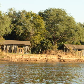 The tented chalets lie on the banks of the river...