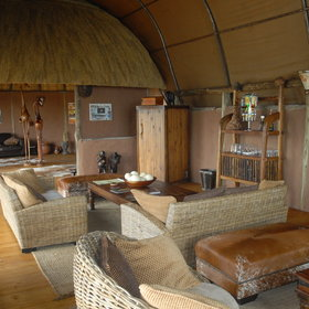 Okuti's lounge area has brick walls and a plastic roof, lined with natural cane.