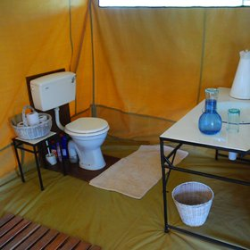 At the rear of each tent, the simple bathroom has a basin, bucket shower and flush toilet.
