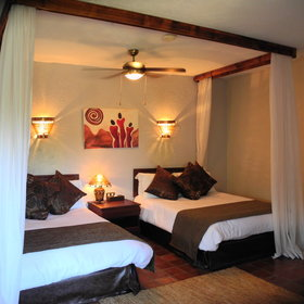 Each room has two double beds surrounded by a large  mosquito net...