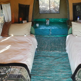 The tent is furnished with comfortable twin beds.