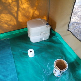 During the night a portable chemical toilet is set up in the partition at the rear of the tent.
