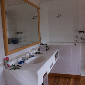 The en-suite bathroom is fully tiled and provides a double washbasin beneath a large mirror.