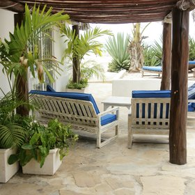Outside, there is a shaded veranda with a comfortable sitting area.