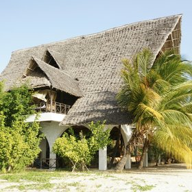 A two-storey banda under a thatched roof hosts the lodge's main areas,…