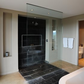 The bathroom contains a stylish shower,…