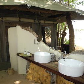 An open air bathroom leads out from the tent and has twin hand basins...