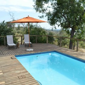 The decent sized swimming pool is situated on a deck and surrounded by sunloungers ...