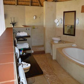 The open en-suite bathroom overlooks the bedroom.