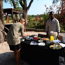 Breakfast is served under the huge ebony trees that shade the camp,...