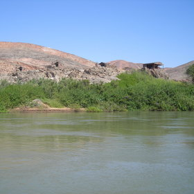 Kunene River Camp is perched on top of large boulders, just above the river bank.