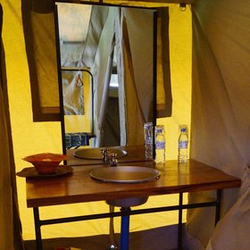 Each tent has an en-suite bathroom with a washstand, …