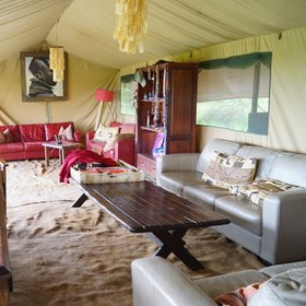 The tent is decorated with leather sofas, chandeliers, chunky wooden furniture, rugs and chests.