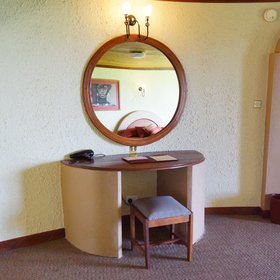 …a desk with a large mirror,…