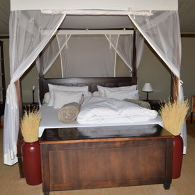 Each one includes a solid wooden bed draped with mosquito nets,…
