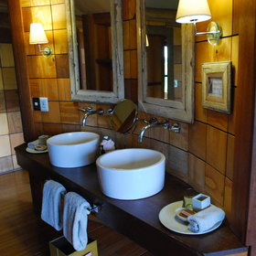 The ensuite bathroom includes two basins and complementary toiletries,…