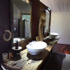 The respectably sized en-suite bathroom includes twin basins,…