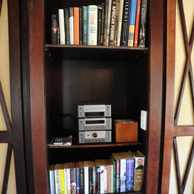 …a bookshelf, a CD-player, a drinks station and a writing desk.