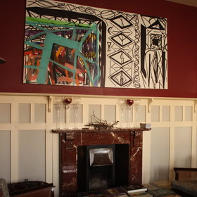 Inside is a lounge with fireplace and some modern artwork on the walls.